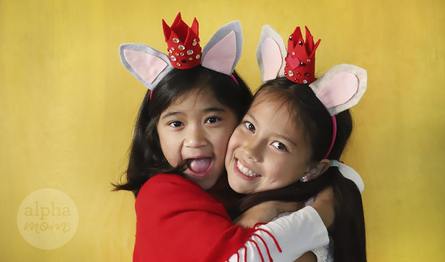 two girls wearing mouse ears and red crown on their headbands in front of a yellow background