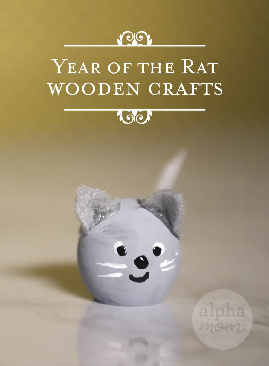 close up of one mini painted wooden mouse with the words Year of the Rat on a golden background
