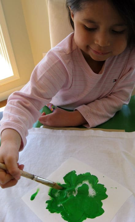 photo of a young girl applying green paint through a shamrock stencil onto a white t-shirt