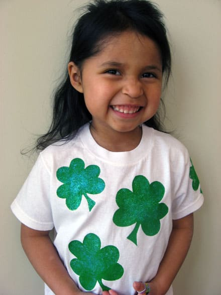 little brunette girl wearing a white t-shirt with glittery shamrock painted on