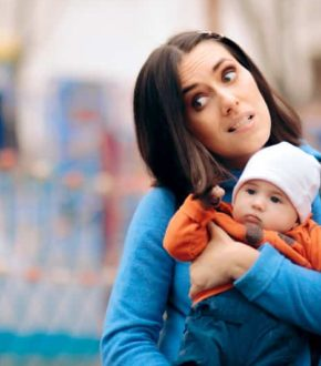 Baby being held by mom and pulling her shoulder-length brown hair
