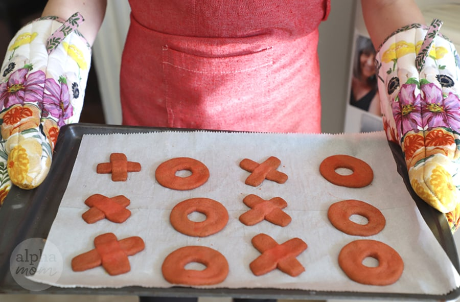 photo of X and O shaped cookies on cookie sheet coming out of the oven