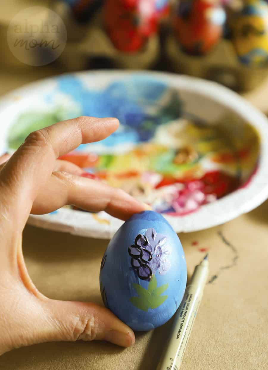 close-up of adding detail to purple flower on blue painted egg
