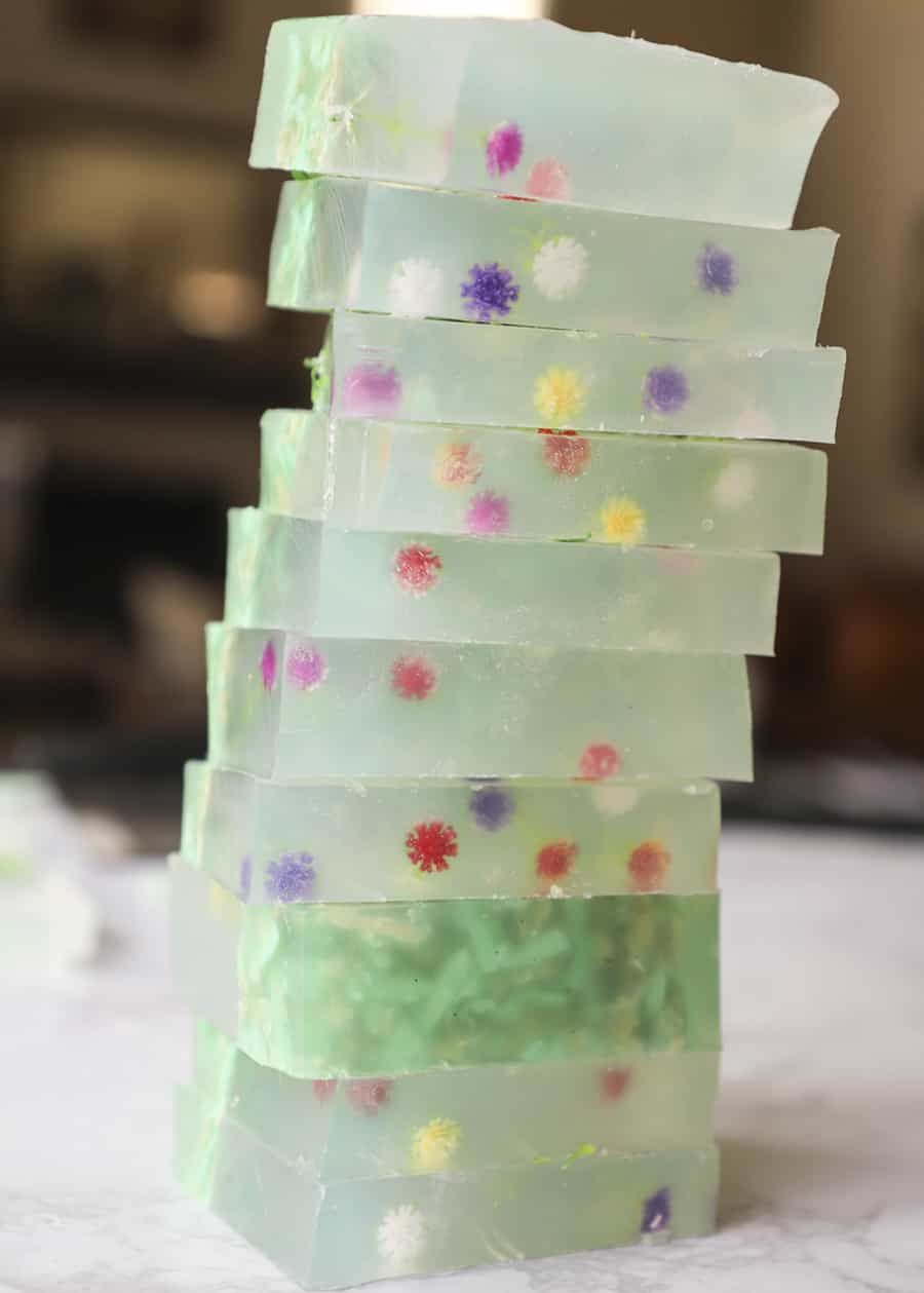 stack of 10 bars of homemade soap with tiny artificial flowers inside of it