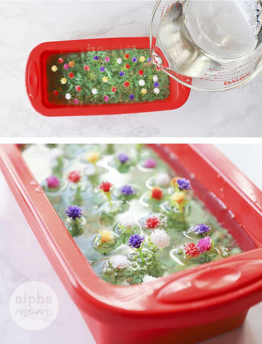 overhead photo of melted glycerin soap in a pyrex being poured into a red loaf pan with flowers to make homemade soap
