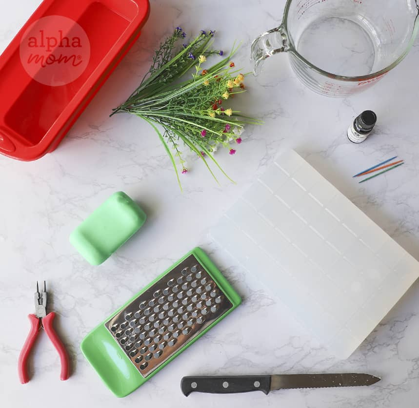 overhead photo of supplies to make homemade soap including glycerin, grater, and artificial flowers