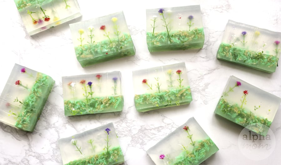 overhead photo of multiple homemade soap bars with artificial tiny flowers in them
