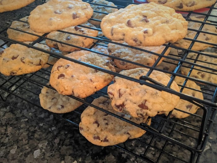 freshly baked chocolate chip cookies on three stacked rows of cooling racks