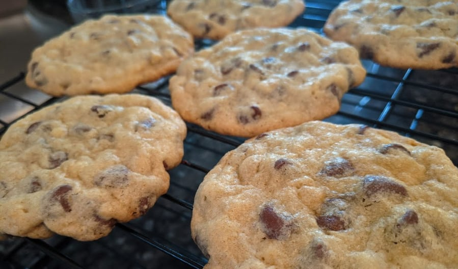 close-up photo of freshly basked chocolate chip cookies on cooling rack