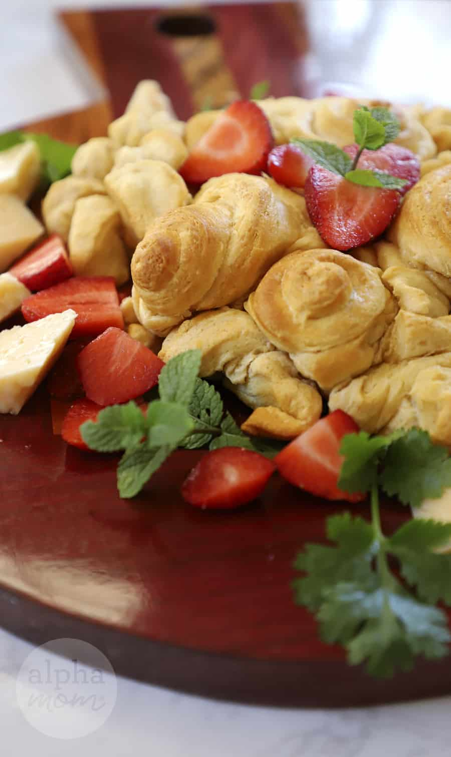close-up photo of baked crescent rolls in the shape of flowers and cut strawberries