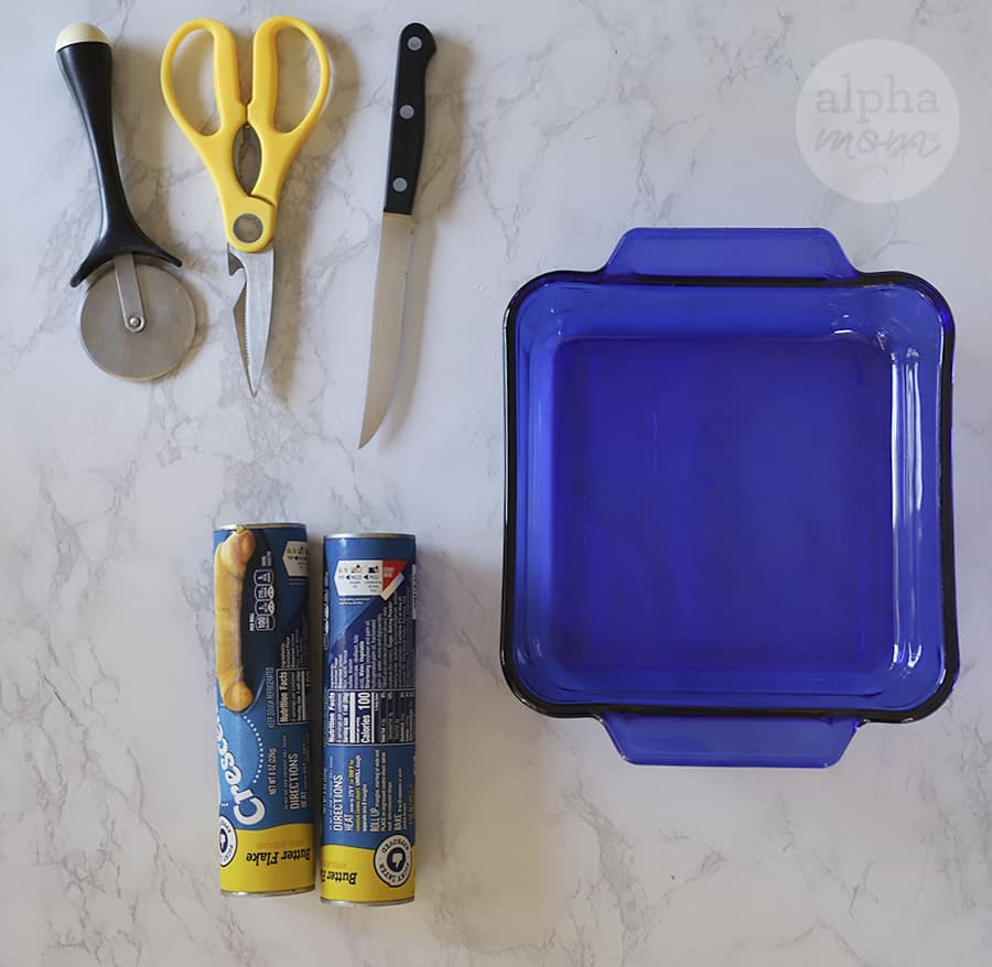 overhead photo of blue baking dish with two crescent roll dough canisters and cooking instruments