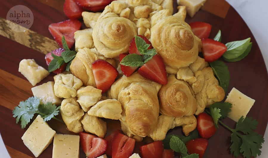 overhead photo of baked crescent rolls shaped into roses on wooden board and sprinkled with cut strawberries