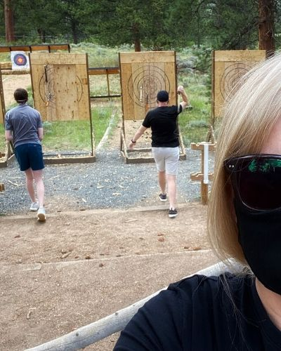 blond woman in foreground with father and teen son throwing axes at target behind her