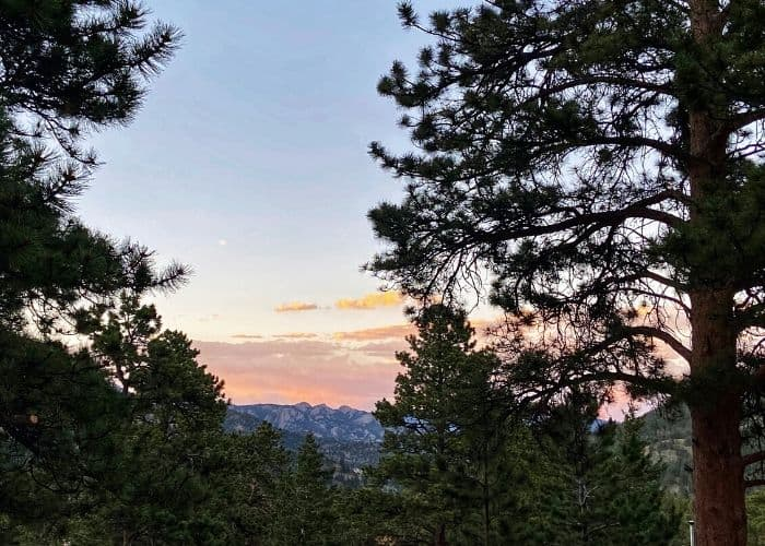 sunset over snowy mountain from hiking view in Colorado Rockies