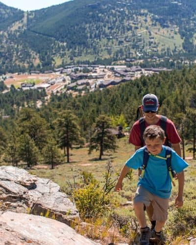 young boy and father hiking in mountains of Colorado