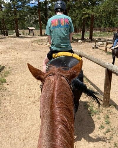 rear view of horse's head and teen boy riding horseback in Colorado