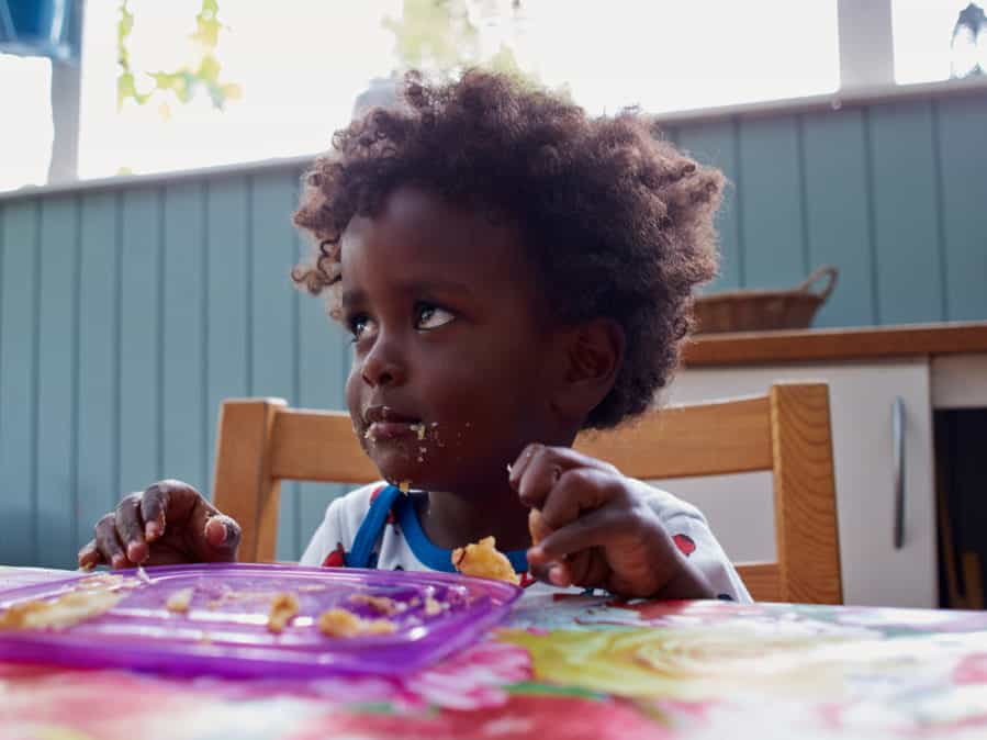 Adorable black toddler eating with food at dinner table