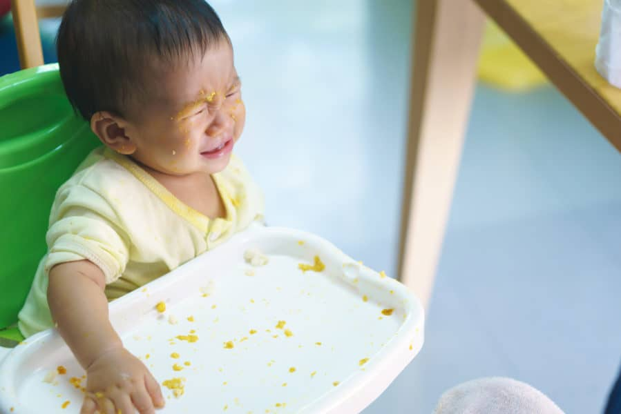 Asian baby in high chair refuses eating food