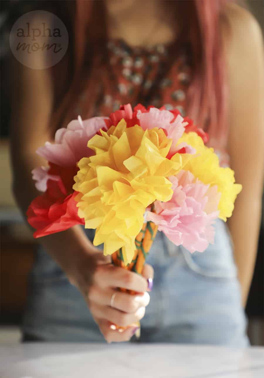 close-up of bouquet of multi-colored tissue paper flowers held by teen girl