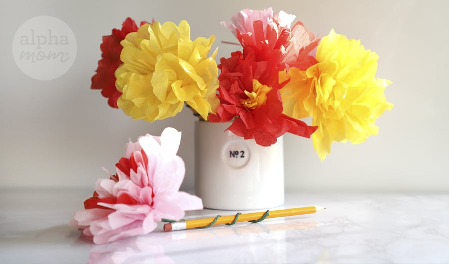 close-up of several pink, red, and yellow paper flower pencil toppers in a mug