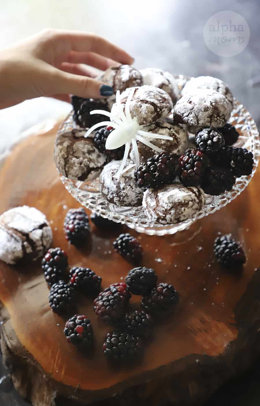 picture of hand reaching for plate of Blackberry Chocolate Crackle Cookies on crystal serving dish