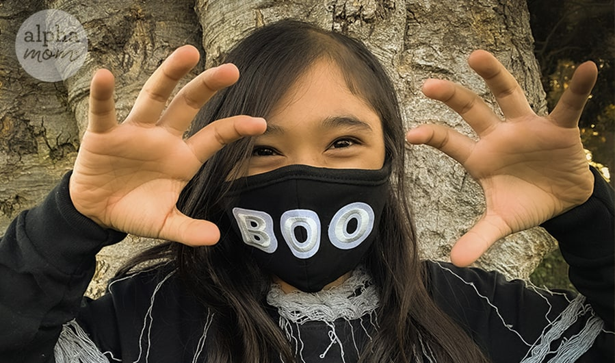 photo of girl wearing black Boo black face mask for Halloween while holding up hands