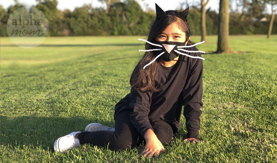 photo of girl outside wearing homemade Halloween cat costume with face mask of craft nose and whiskers