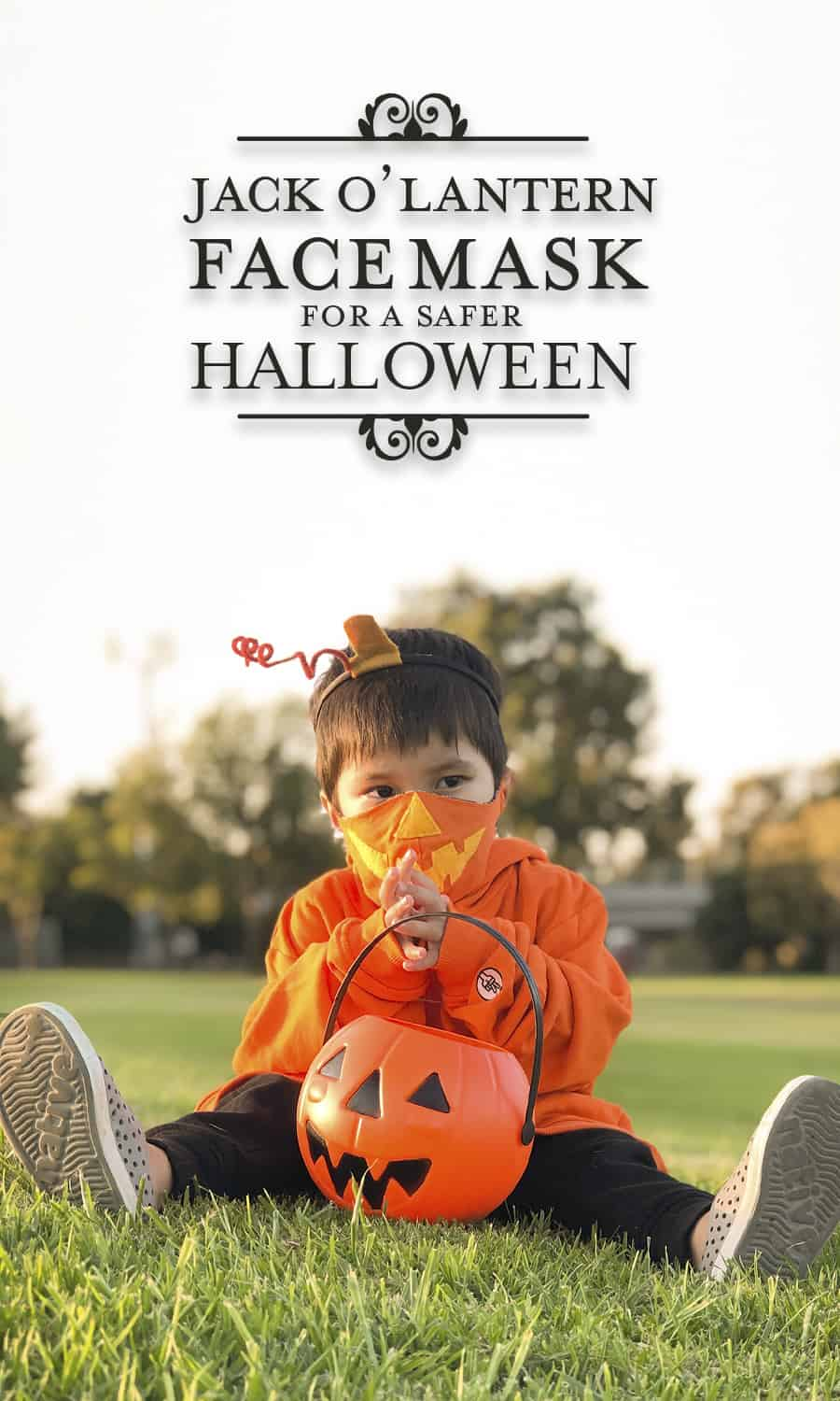 photo of young boy sitting in park wearing a jack-o-lantern face mask Halloween costume with a candy bucket