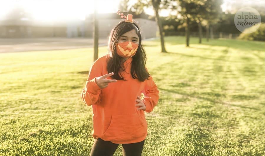 girl wearing jack o' lantern face mask as Halloween costume