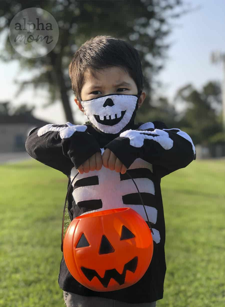 photo of young boy wearing homemade skeleton Halloween costume with skull face mask covering mouth and nose for COVID and holding a plastic pumpkin bucket
