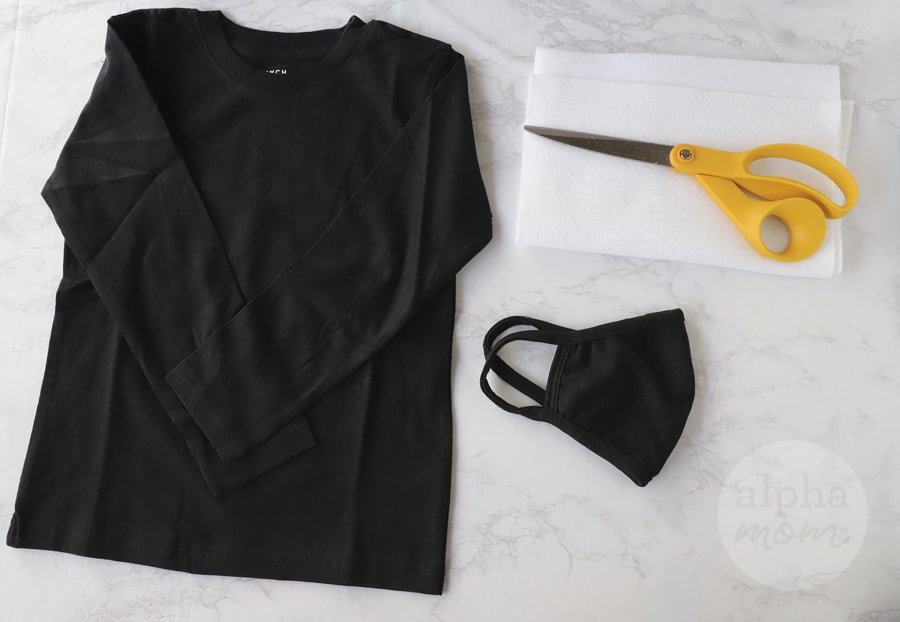 overhead photo of long-sleeve black t-shirt,black cloth face mask, and white felt and fabric scissors