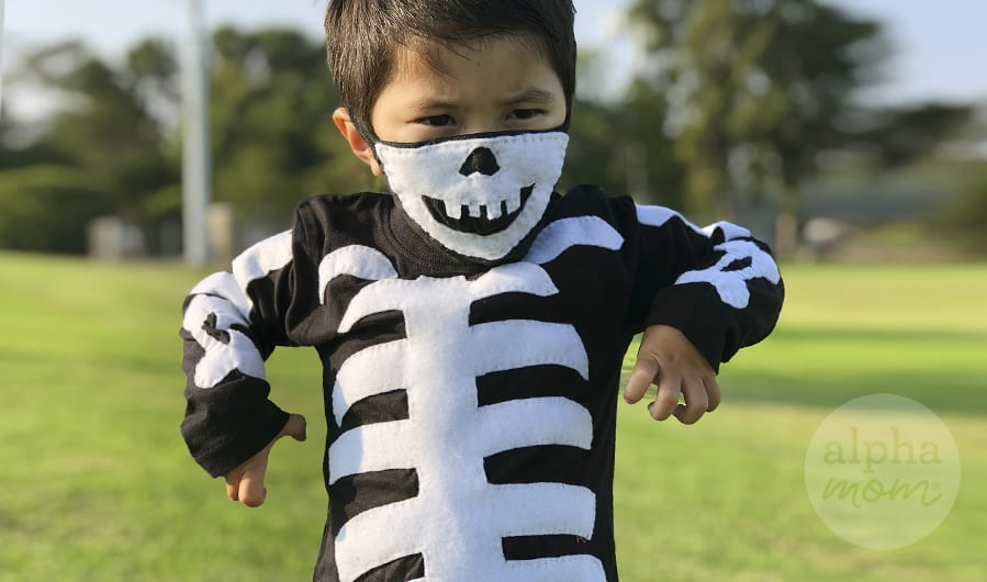 young boy outside wearing homemade skeleton Halloween costume with skull face mask protection for COVID