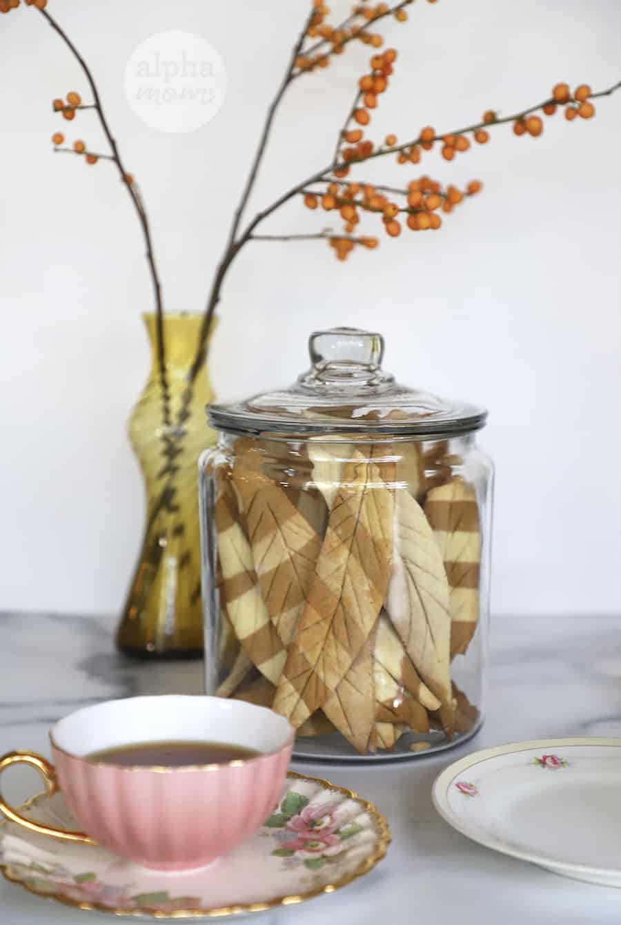 feather-shaped striped sugar cookies stored in a large Anchor Hocking jar with tea cup in foreground