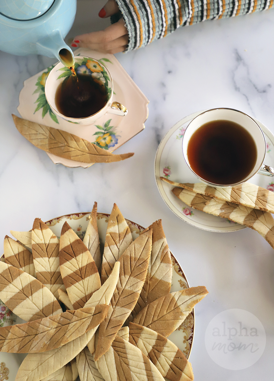 overhead photo of feather-shaped striped tea cookies on a plate and next to saucer