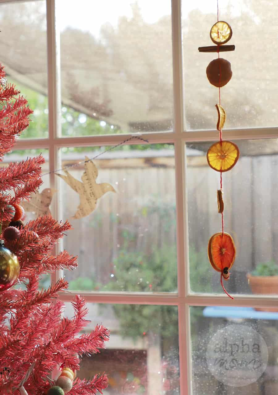 citrus suncatcher garland in front of the window near a pink artificial tree