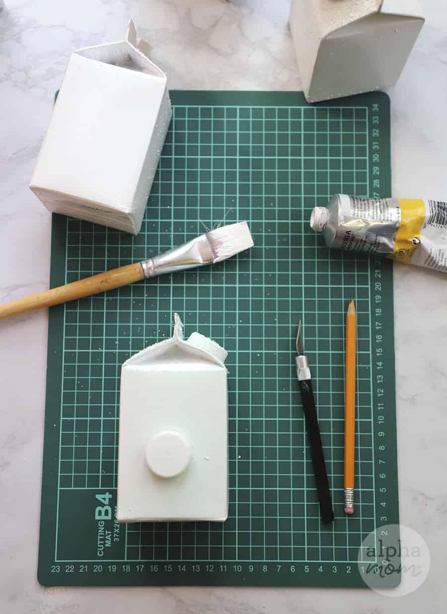 overhead photo of pint-sized milk carton and paint brush on green mat