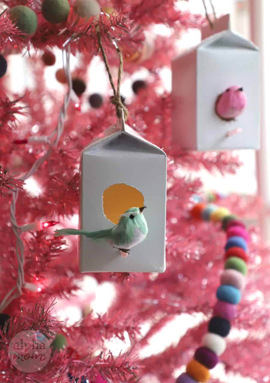 close-up of DIY birdhouse ornament made from creamer carton on pink Christmas tree