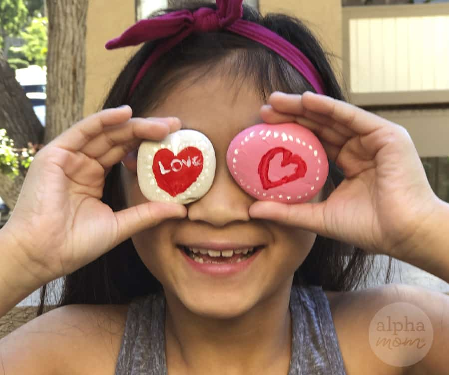 close-up photo of girl holding up two hand painted rocks with Love and and hearts for Valentine's Day in front of her eyes