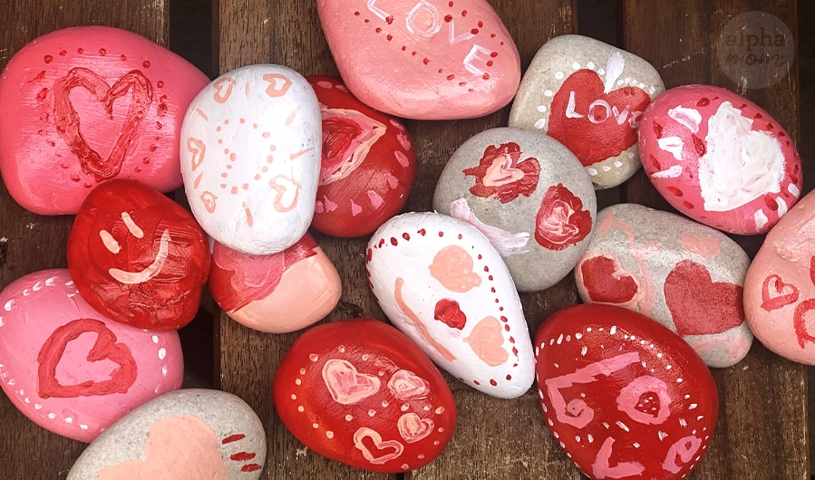 overhead photo of many hand painted red, pink, and white rocks with Valentine's Day messages