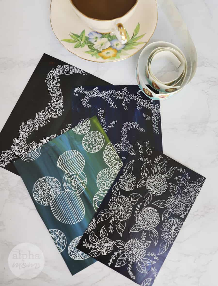 overhead photo of finished doodle art postcards with roll of stamps and cup of tea to the side