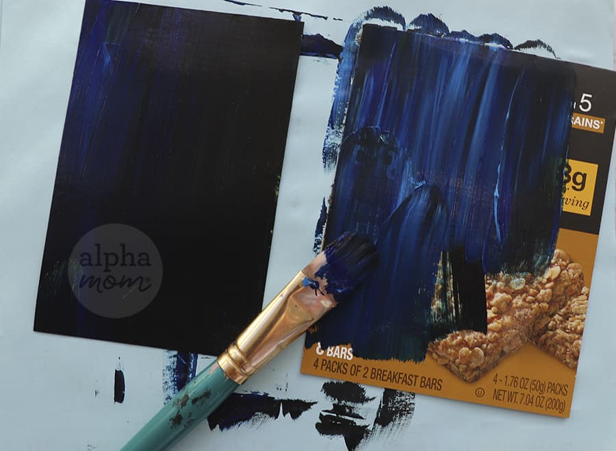 overhead photo of dark blue paint being brushed onto cardboard box paper