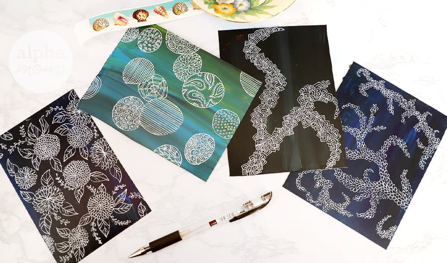 close-up pohoto of four doodle art postcards with pen and stamps