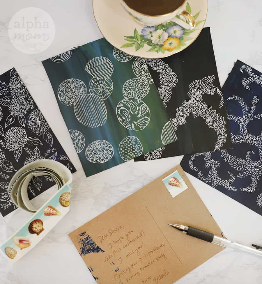 close-up photo of postcard being written with four more doodle art postcards and stamps on the side