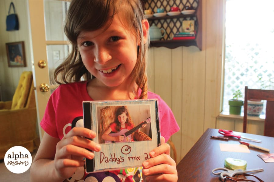girl holding a homemade Dad's Mix CD