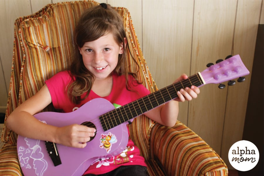 Girl sitting in a chair and playing a purple guitar