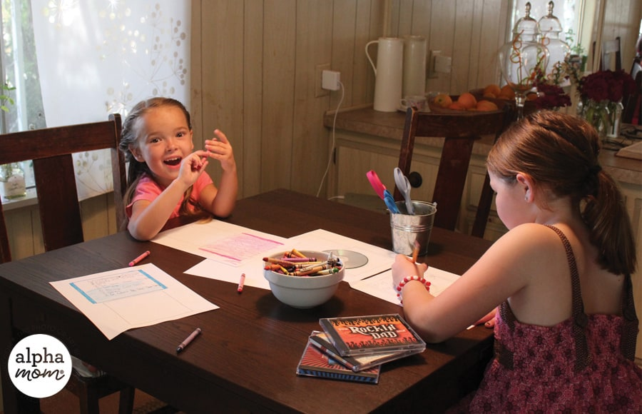 two girls seated at a table coloring on paper