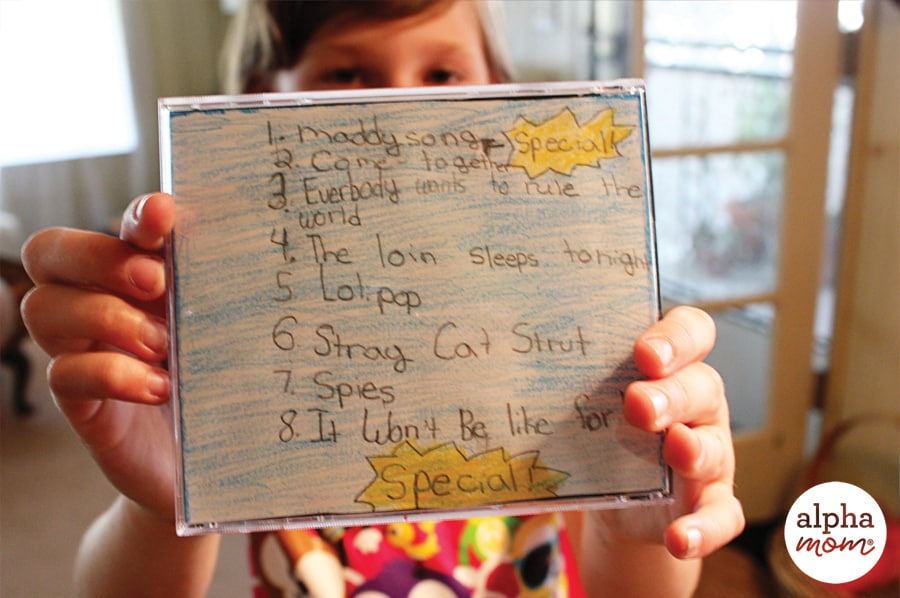 girl holding up handwritten playlist for CD cover in front of her