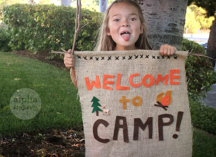 young girl holding up large Welcome to Camp Banner and sticking out her tongue