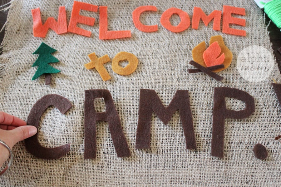 adding Welcome to CAMP felt letters to burlap for banner