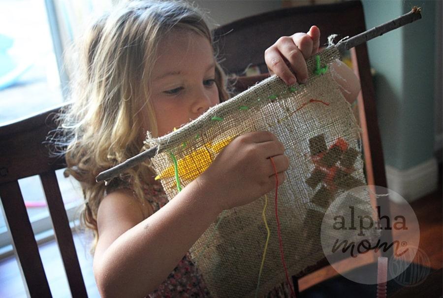 Child sewing carefully onto burlap banner